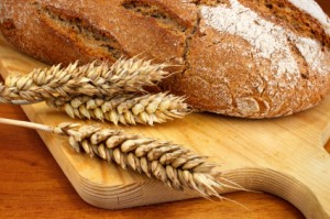 *** Local Caption *** Fresh baked loaf with wheat ears on wooden breadboard